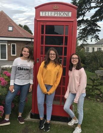 Adolescentes devant une cabine téléphonique rouge en Angleterre
