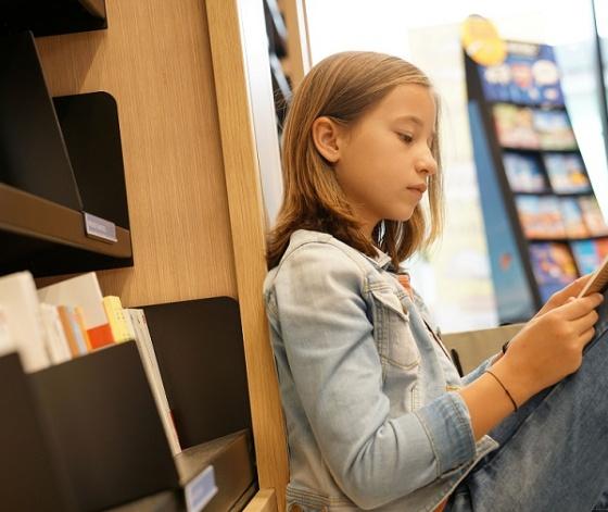 Jeune fille assise dans une librairie avec une bande dessinée