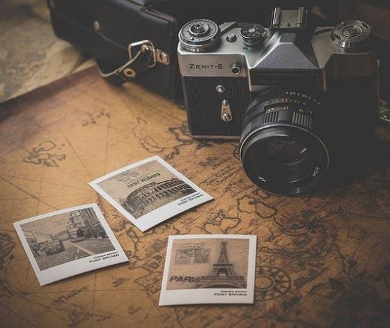 Vieil appareil photo posé devant des photos de vacances
