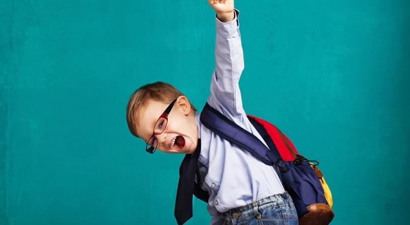 Jeune écolier content de reprendre le chemin de l'école