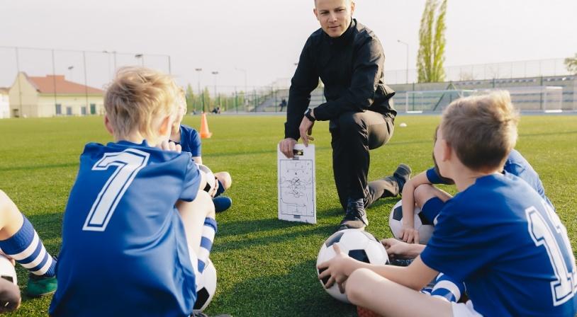 Entraîneur de foot entouré d'enfants