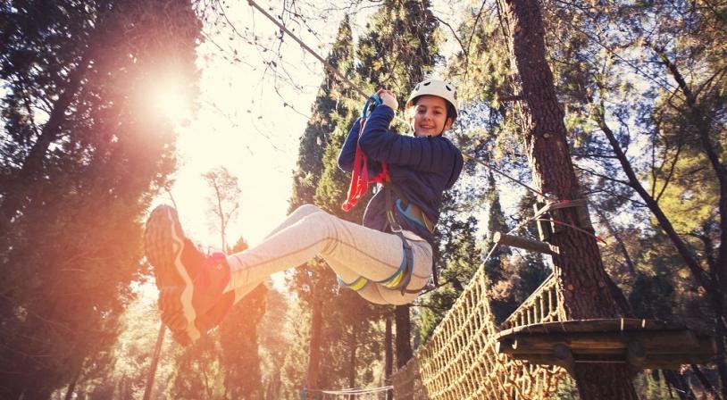 Jeune fille faisant de la tyrolienne dans un parc d'aventure accrobranche