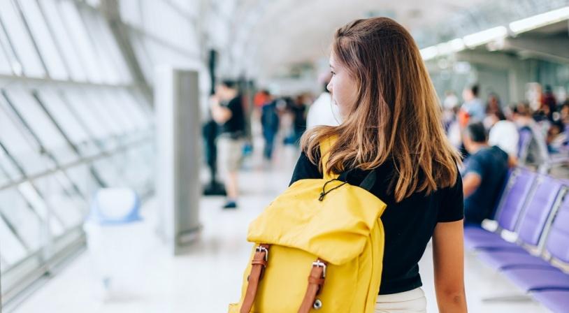 Jeune fille attendant avec un sac jaune son avion pour partir en séjour linguistique