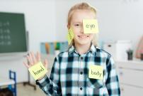 Ecolière apprenant l'anglais avec des post it sur les différentes parties de son corps
